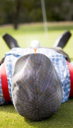 Golfer Relaxes Laying Down On A Golf Green Near The Ninth\ Hole With A Golf Tee And Golf Ball In His Mouth In A Sporting\ Concept With Copyspace On His Flat Cap