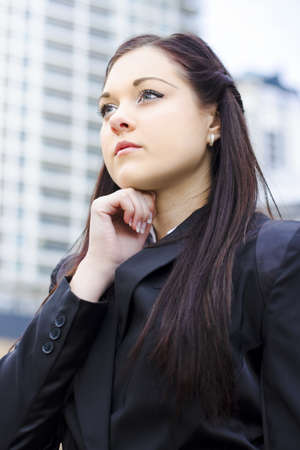 Half Body Portrait Of A Young Business Woman Standing Is The City Center Holding Hand To Head In An Expression Of Grand Business Ideas Stock Photo - 13262141