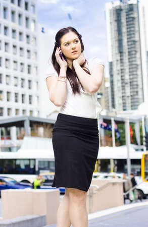 Young Confident Modern Business Woman Standing Chatting Talking And Listening To A Phone Call On A Busy City Street In A Office Telecommunication Concept photo