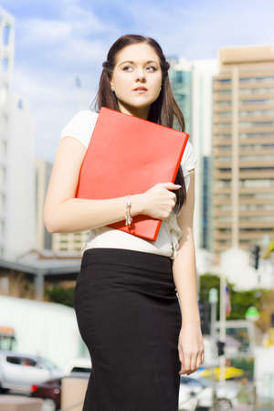 Sad Distressed And Devastated Young Business Woman Crying And Sobbing While Walking With Red Folder In Hand In A Sad And Unhappy Business Concept photo