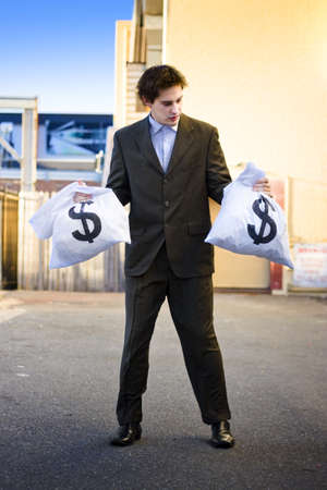 Financial Planning Concept With An Unsure Business Man Looking For Help And Advice On Where To Invest His Bags Of Money Wealth And Profit Stock Photo - 13262423