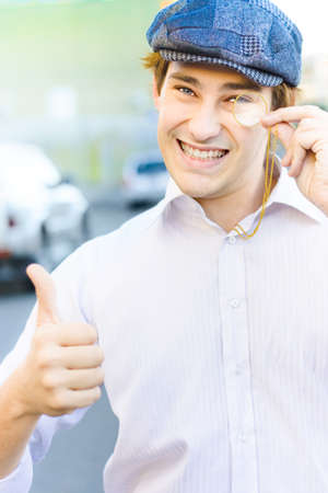 Lively Animated And Smiling Vintage Man With Monocle Gives An Optimistic Gesture Of Acceptance With A Thumbs Up In A Depiction Of Good Old Fashioned Business photo