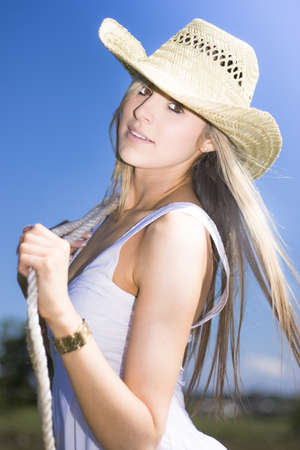 Half Body Portrait Of Attractive Young Woman With Rope And Cowboy Hat In Countryside Blue Sky Background photo