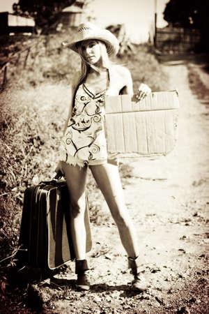 Vintage Sepia Image Of A Rustic Hitchhiker Hitching A Lift On The Side Of An Old Outback Road While Holding A Cardboard Sign photo