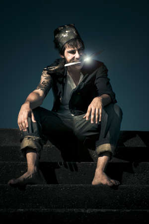 Dark And Scary Portrait Of A Evil And Devious Pirate Sitting On A Stairwell During Twilight With Moonlight Reflecting On A Knife Held In His Mouth Stock Photo - 13359700