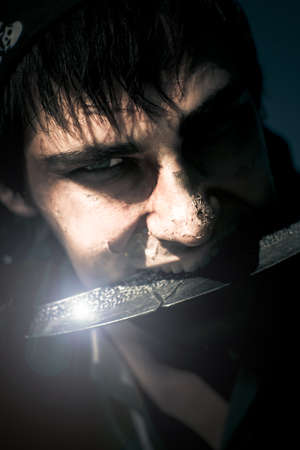 Terrifying Horror Face Portrait Of A Scarred And Blistered Pirate Biting On A Razor Sharp Sword Blade In A Frightening Fear And Danger Concept photo