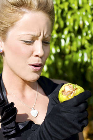 Standing In The Garden Of Eden Eve Takes A Bite Out Of A Chosen Forbidden Fruit Only To Discover With A Look Of Disgust That This Lovely Green Apple Is Rotten To Its Core photo