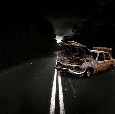 Smashed Up And Wrecked Car With Deflated Tyres, Missing Headlights And Dented Front Bumper Bar Parked In The Middle Of A Dark Highway Street photo