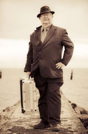 Nostalgic Photograph With Slight Solarisation Of A Vintage Traveling Business Man Wearing Suit And Tie With Metal Suitcase While On A Travel Tour Of Olden Days Stock Photo - 13360369