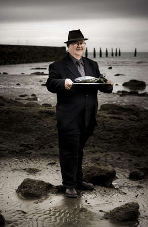 Elderly Restaurant Waiter Holding A Silver Platter Of Fish When Serving Up A Fishermans Seafood Platter On A Rocky Beach Sea Shore Stock Photo - 13360861