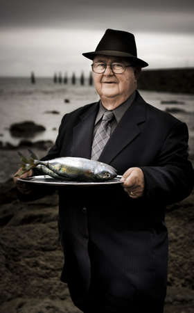 Serious Man At Dark Beachfront Holding A Plate Of Fish With A Questioning Expression In A Fisheries Over Consumption Of Natural Resources Stock Photo - 13360282