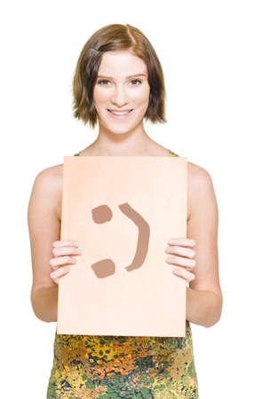 Smiling Woman Holding A Business File With A Emocon Happy Face Painted On The Front In A Positive Thinking And Happiness Concept, Isolated Over White photo