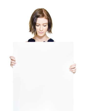 Portrait Of An Attractive Young Business Woman Holding A Blank Billboard While Looking Down To See The Message, Copyspace Concept Isolated On White photo