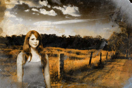 Cracked And Distressed Image Of A Happy Young Country Girl With Auburn Hair Standing At A Rural Farm Location During Sunset photo