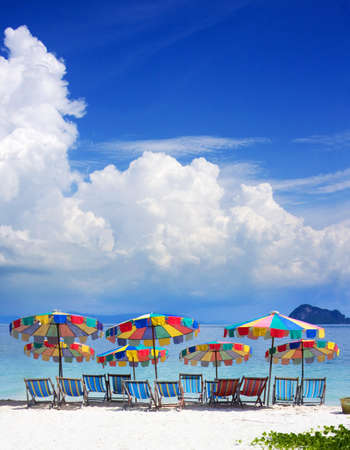 Tropical Holiday Destination With Colorful Umbrellas Or Parasols On Sandy Beach Paradise With Sea And Cloudscape In Background photo