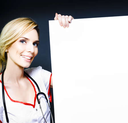 Enthusiastic smiling healthcare professional such as a doctor, dietician or nurse, holding a blank white board or poster for your advertising or announcement photo