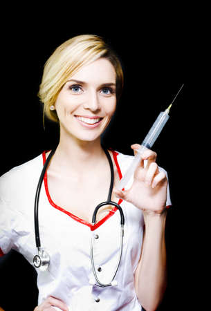 Smiling female doctor with big syringe on black background photo