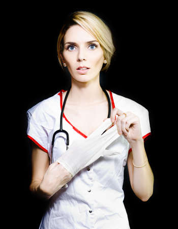 Serious young nurse with short blonde hair removing her latex gloves after doing blood work on a patient photo