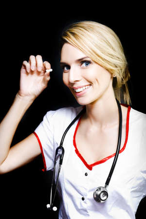 Smiling young blonde nurse with a stethoscope around her neck holding a pill for a aged care patient, on dark background Stock Photo - 13453504