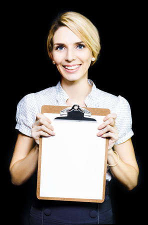 Smiling enthusiastic professional woman holding a clipboard with a blank sheet of paper for your attention as she conducts a survey, customer services questionnaire, or training photo
