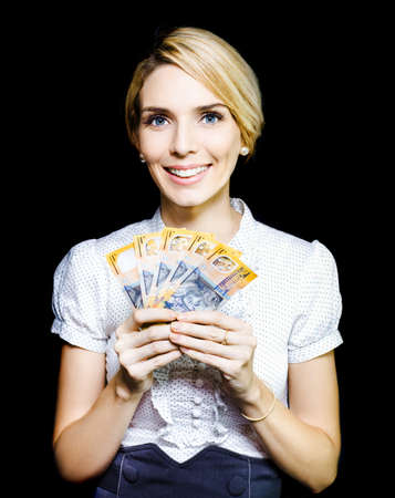 Attractive blonde business woman holding a cash bonanza of banknotes in her hand which she has won in an unexpected windfall and for which she is truly appreciative photo
