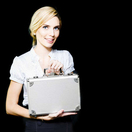 Young business lady pleased at her promotion and new higher security clearance displays her new badge of office, a metal attache case for transporting high level restricted access documents Stock Photo - 13521478