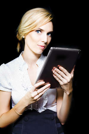 Beautiful stylish professional blonde woman holding a touch screen tablet with the screen facing herself and looking up with an attentive assessing expression on a black studio background photo