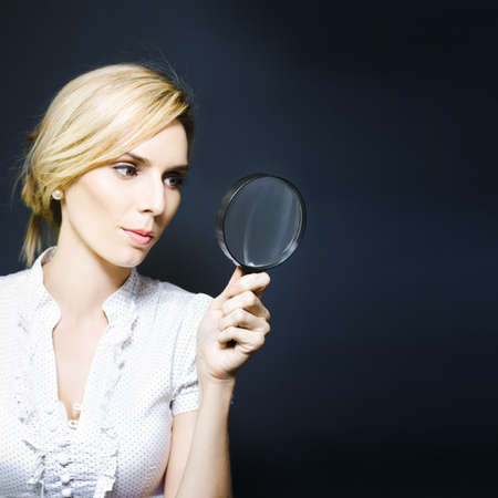 Business woman with magnifying glass, concept of a crime scene detective searching for clues, scientific research, quest for answers or conducting an inspection Stock Photo - 13521481
