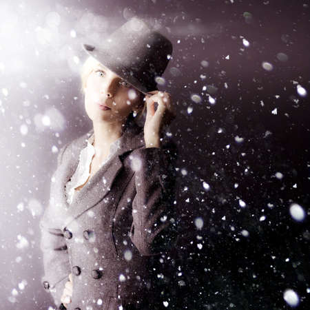 A mysterious woman operative in a hat and coat stands waiting out in a snowstorm as she watches and spies on her assigned target Stock Photo - 13521483
