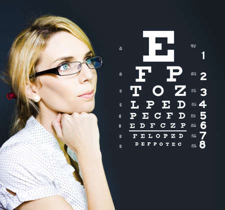 Photo Of A Beautiful Blonde Business Optician Or Optometrist Wearing Eye Wear Glasses Looking At Number And Letters On A Ophthalmology Chart To Check Eyesight Stock Photo - 13587504