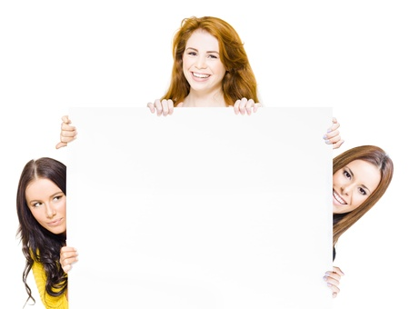 Three happy women full of femininity, vitality and zest peering round a large blank white promotional sign to attract your attention and approval of a product or promotion Stock Photo - 13587373