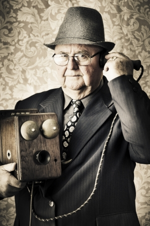 Image of a old fashioned vintage business man standing in a office communicating to the exchange through a retro box telephone in a technology concept photo
