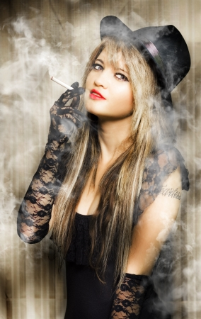 beautiful vintage girl smoking cigarette with pretty smile in a creative pinup style portrait  Stock Photo - 13865141