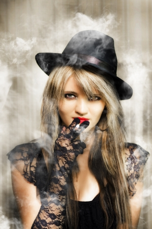 Edgy fifties portrait of smoking hot young beautiful sexy underworld gangster woman in retro lace outfit with glamorous make-up and hairstyle photo
