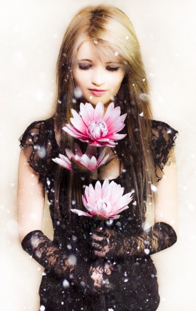 Creative portrait of a beautiful young woman in elegant fashion holding a delicate flower in the falling snow of winter photo