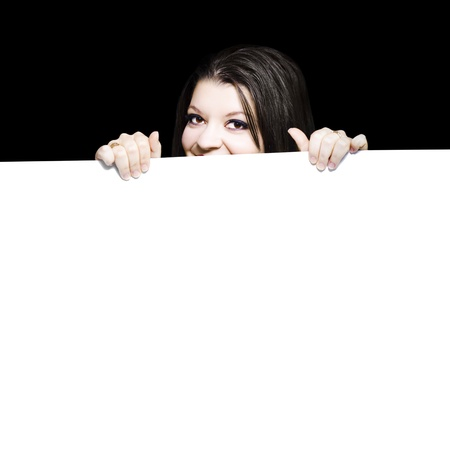 Young woman peeping over the top of a blank white placard that she is holding in her hands ready for your advertisement, promotion, announcement or marketing text photo