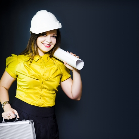 Young confident smiling female architect in a hard hat carrying the building blueprints rolled up over her shoulder on a site inspection on a construction site, conceptual studio image photo