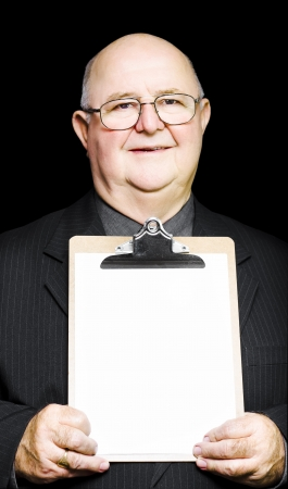 A senior pensioner with a grandfatherly kind-hearted face holds a clipboard with a blank white sheet of paper for your text or advertising in a marketing concept Stock Photo - 14041819