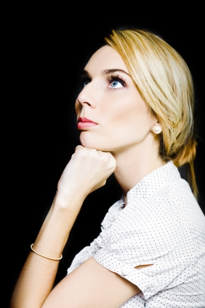 Young attractive woman in business clothing looking at copy-space thinking or dreaming on black background photo
