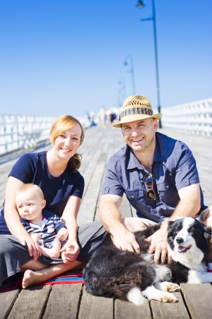 Mum, Dad, baby son and pet collie smiling happily while enjoying the summer sunshine sitting on a pier Stock Photo - 14053893