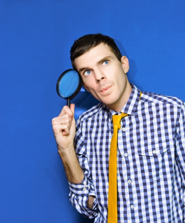 Man Holding Magnifying Glass Looking Up photo
