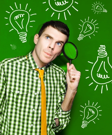 Male Thinking With Spy Glass To Face In Front Of A Green Light Bulb Background photo