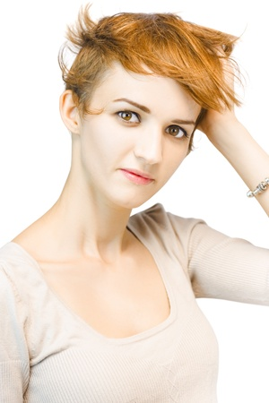 Studio portrait of a beautiful redhead woman looking directly at the camera with a serious expression while running her hand through her short auburn hair Stock Photo - 14247239