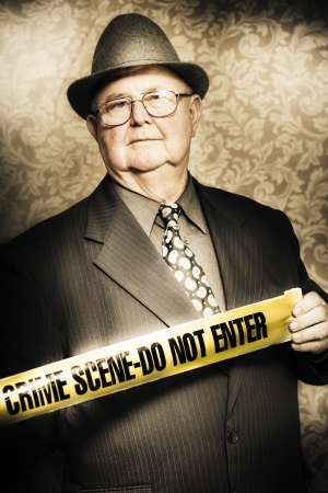 Artistically aged portrait of an astute fifties crime investigator with a stoical expression watching carefully for any clues or odd behaviour as he unwinds the yellow tape at a fresh crime scene photo