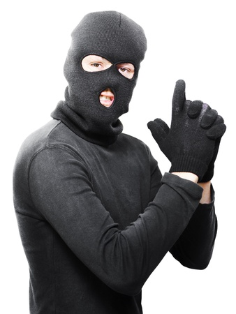 Male criminal in mask making a hand gun gesture in a depiction of a armed holdup or robbery isolated on white background photo