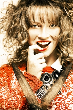 Fifties Fashion Photo Of A Young Brunette Woman With Curly Hair And Bright Red Makeup Holding Gardening Hedge Clippers In A Hairstyle And Hairdressing Concept photo