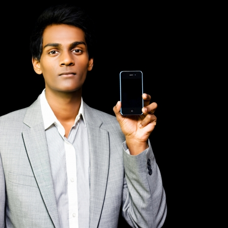 Asian business salesman in suit holding mobile phone on black background photo