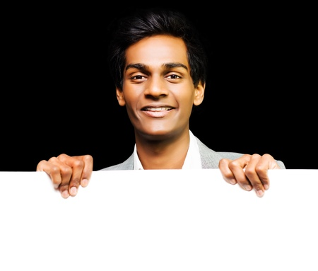 Smiling charismatic young Asian marketing executive promoting copyspace and publicity on the large blank white banner or placard that he is holding Stock Photo - 14344068