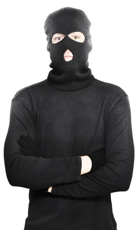 Young thug turned criminal posing with his arms folded wearing a black outfit with hooded mask to conceal his identitiy, isolated on a white studio background Stock Photo - 14344071
