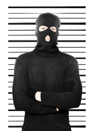Mugshot of a busted thief caught in the act of petty larceny standing dejectedly in front of a police background as he is apprehended yet again as a repeat offender Stock Photo - 14344075
